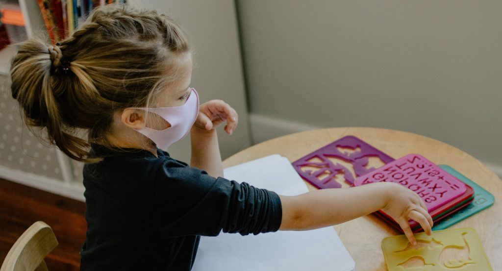 Young girl wearing mask while completing a Head Start activity